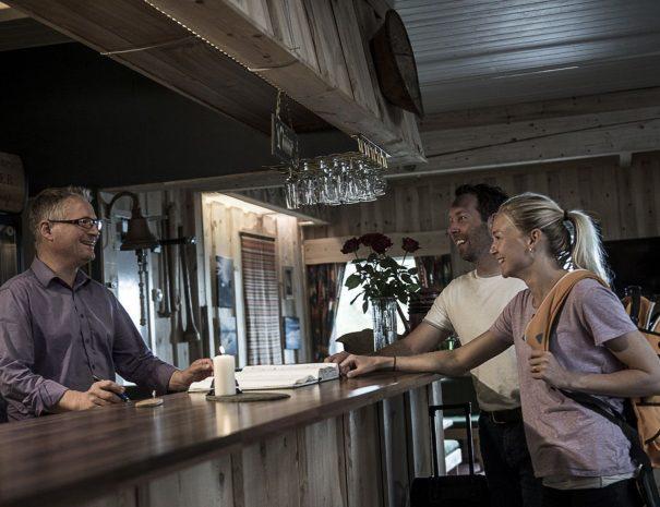 Et par ved baren med verten bak disken.