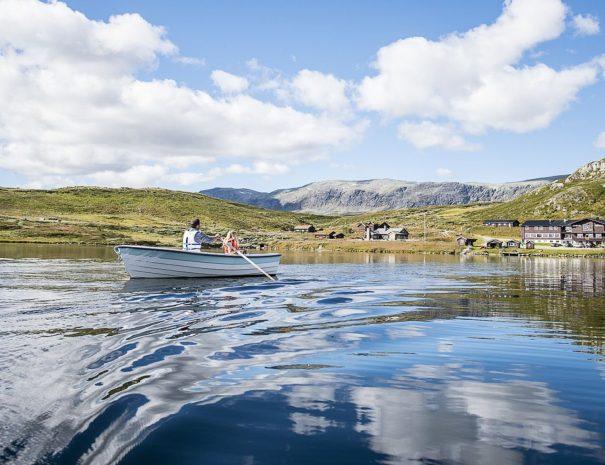 Båt på vannet med fjellstua i bakgrunn