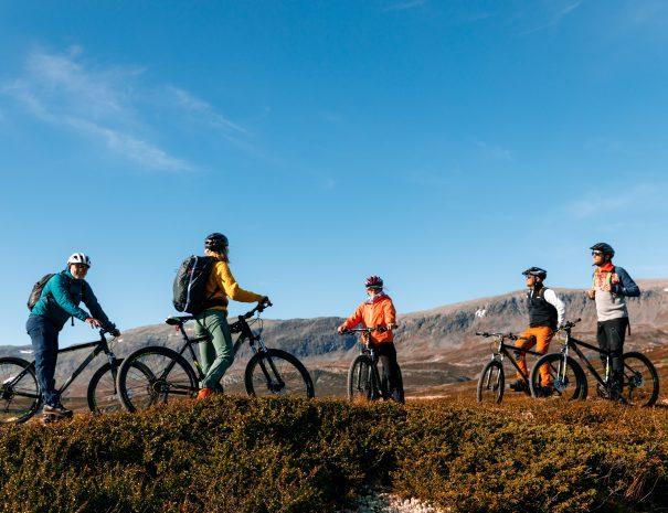 Gruppe på sykkeltur med fjell i bakgrunn. Høstfarger og klar blå himmel.