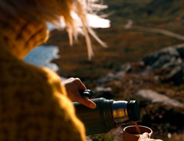 Sjenker kaffe fra termos i trekopp på fjelltopp i ettermiddagssola.