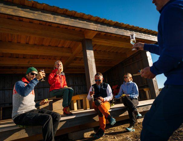 Gruppe sittende i gapahuken, skåler i bobler en klar høstdag
