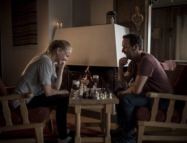 Par som spiller sjakk foran peisen i peisestua