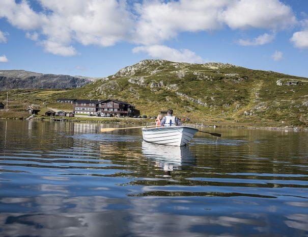 Robåt på Bergsjøen med to personer i og fjellstua og Reineskarvet i bakgrunn
