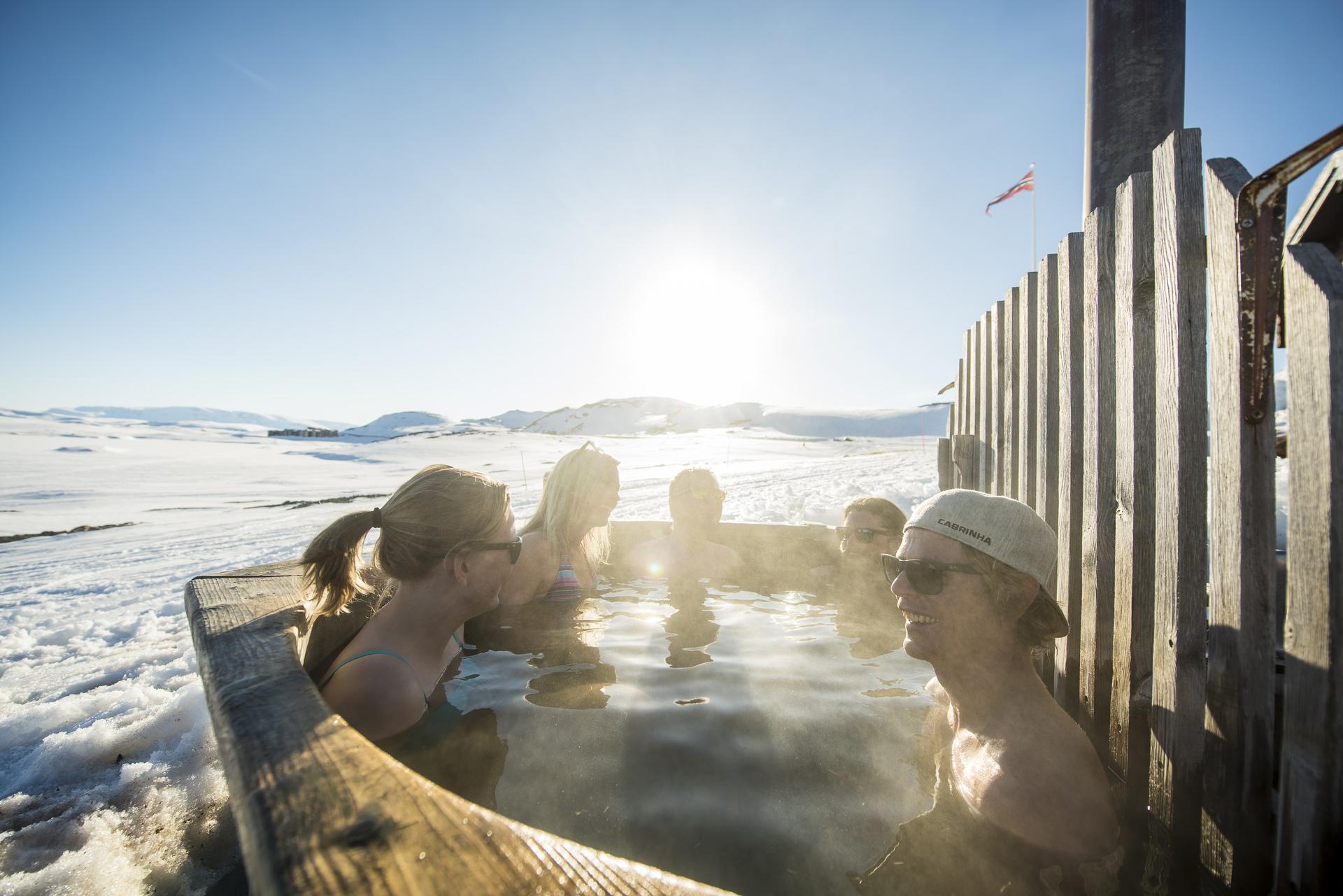 Gjeng i badestampen, rykende vann og snø i bakgrunn, norskt flagg som vaier i fjellheimen