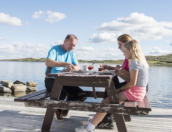 Familie som spiser vafler med rømme på benken i sola ut mot Bergsjøen en klar og stille sommerdag